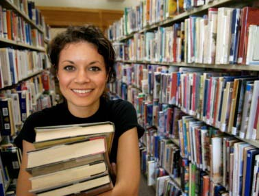 Pic of student holding books in the Library
